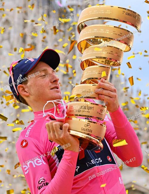 British cyclist Tao Geoghegan Hart of UCI WorldTeam Ineos Grenadiers lifts the trophy on the podium after winning the 103rd Giro d'Italia cycling race
