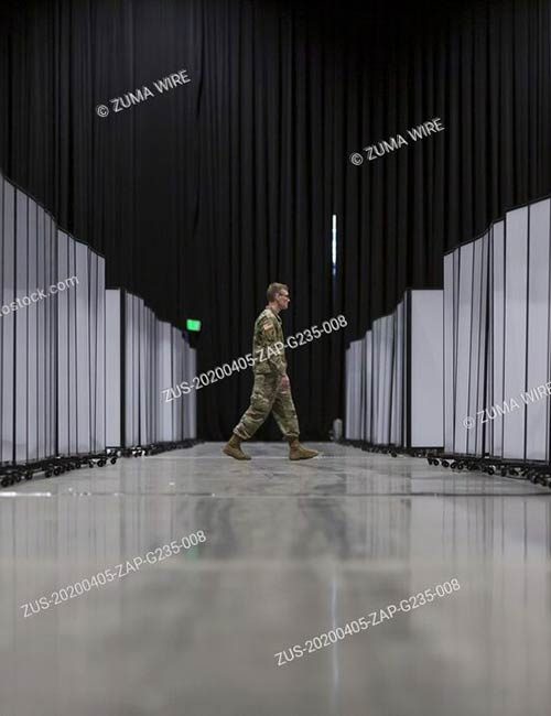 A soldier walks past partitions hiding rows of hospital beds at the field hospital in CenturyLink Field Event Center in Seattle
