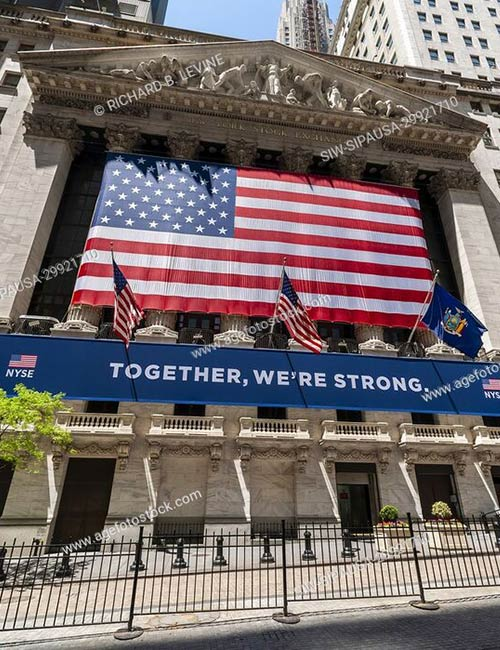 A giant American flag and a Together, We're Strong banner, across the facade of the New York Stock Exchange the day it reopens after being closed for the Covid-19 pandemic