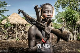 Portrait of a young mursi man holding a kalashnikov, Omo valley, Ethiopia.