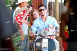 Couple with shopping bags riding on moped