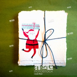 Parcel of hand made christmas labels with a drawing of a father christmas with a presents box.