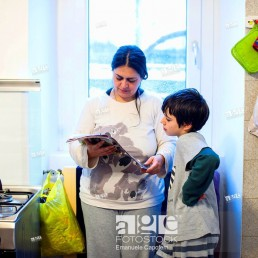 Mother and son reading magazine in the kitchen at home