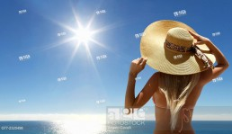 Woman with hat on the beach under sunshine