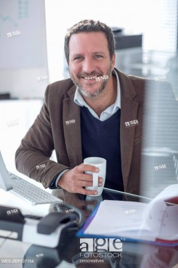 Portrait of smiling businessman at desk
