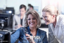 Two smiling women in office looking at computer screen