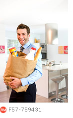 Businessman arriving home with groceries