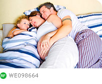 Young family snuggling together in bed
