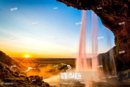 Iceland landscape, Seljalandsfoss waterfall at sunset, picture taken from behind the fall with sunburst.