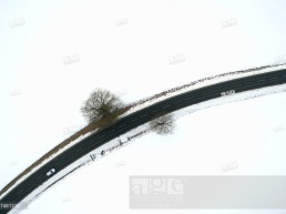 A car drives down a street which is surrounded by snowy grounds near Bad Driburg, Germany, 24 January 2017. Aerial view taken with a drone.