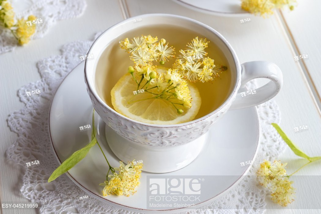 A cup of herbal tea with fresh linden flowers and lemon