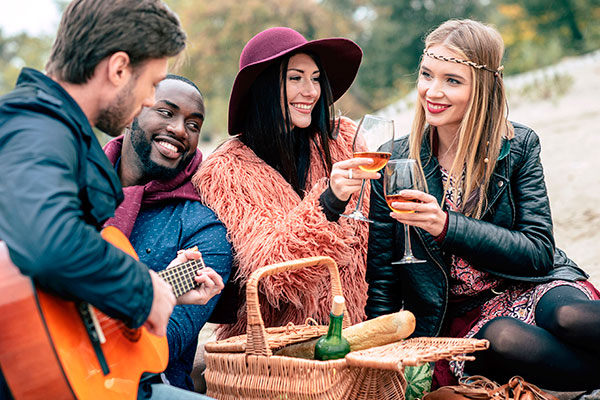 Happy smiling friends holding wine glasses and enjoying guitar while sitting on sandy beach at alfresco picnic