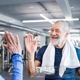Happy senior man and woman high fiving after working out in gym