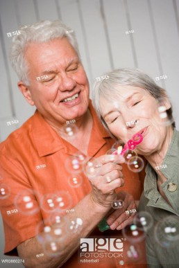 Close-up of an elderly couple blowing bubbles with a bubble wand