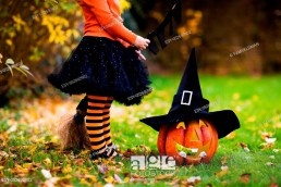 Little girl in witch costume playing in autumn park. Child having fun at Halloween trick or treat