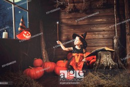 Halloween. little witch child conjures with book of spells, magic wand and pumpkins